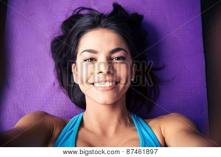 Closeup portrait of a smiling young woman lying on the yoga mat at gym. Looking at camera