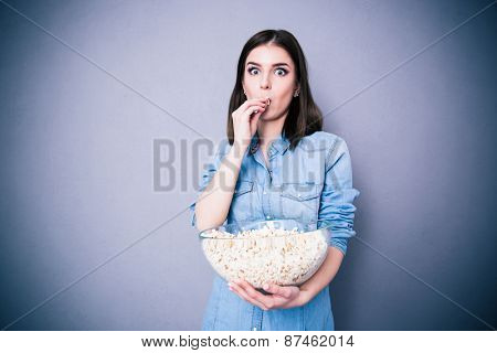 Amazed beautiful woman eating popcorn over gray background and looking at camera