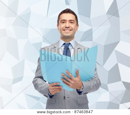 business, people, finances and paper work concept - happy smiling businessman in suit holding open folder over gray graphic low poly background