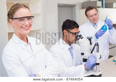 Smiling scientist looking at camera while colleagues working with microscope in laboratory