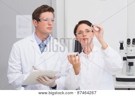 Scientists looking attentively at pill in laboratory