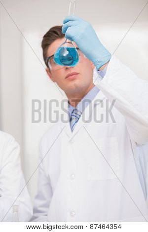 Scientist looking at beaker with blue fluid in laboratory