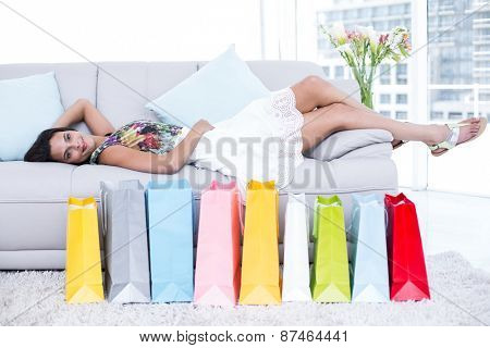Smiling beautiful brunette lying on the couch with shopping bags around her in the living room