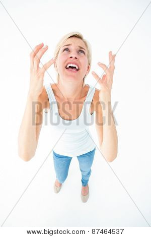 Upset woman yelling with hands up on white background