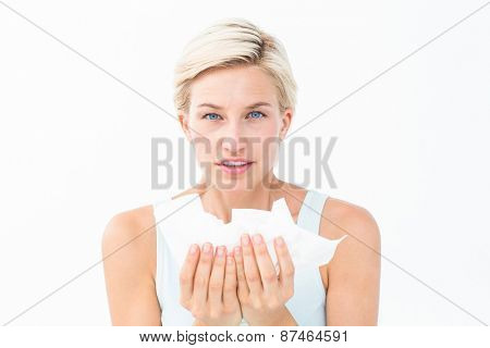 Sick woman holding tissues looking at camera on white background