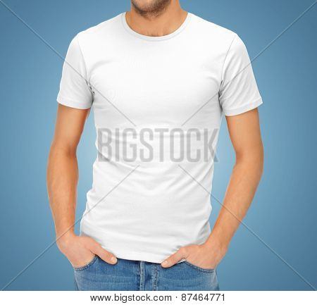 clothing design, advertisement, fashion and people concept - close up of ma in blank white t-shirt over blue background
