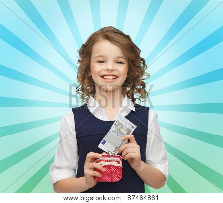finances, childhood, people and savings concept - happy little girl with purse and paper euro money over blue burst rays background