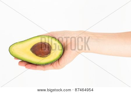 Woman presenting half of an avocado on white background
