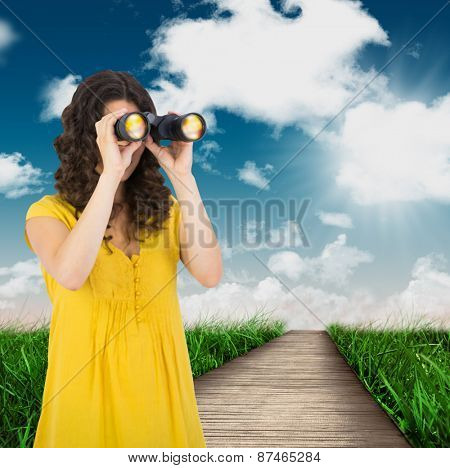 Casual young woman using binoculars against road leading out to the horizon