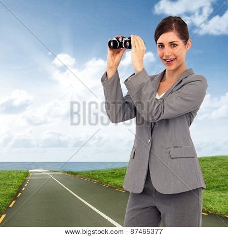 Businesswoman posing with binoculars against road leading out to the horizon