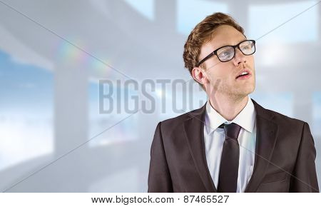Young businessman thinking and looking up against bright white room with windows