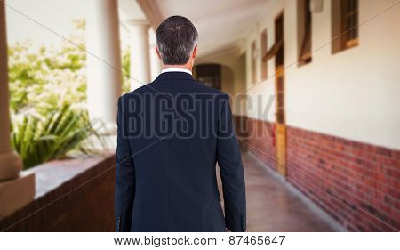 Businessman in suit holding a briefcase against hallway