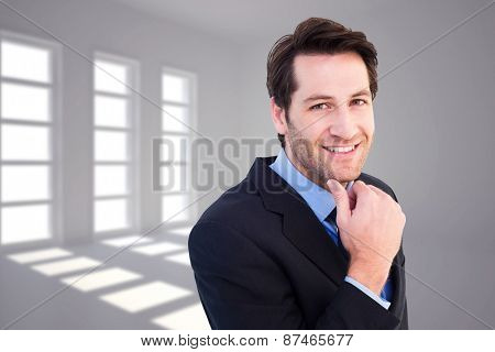 Businessman touching his chin while smiling at camera against dark white room