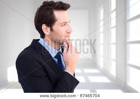 Thinking businessman touching his chin against white room with squares at wall