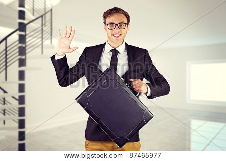 Young geeky businessman holding briefcase against digitally generated room with winding stairs