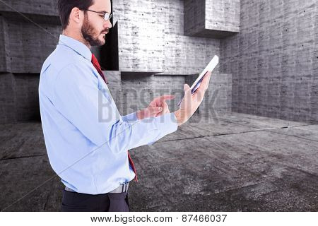 Businessman scrolling on his digital tablet against abstract room