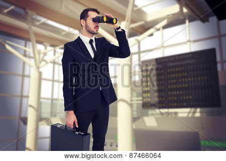 Businessman holding a briefcase while using binoculars against airport