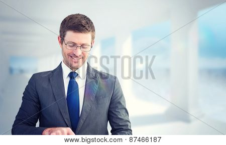 Businessman using his tablet pc against bright white room with columns