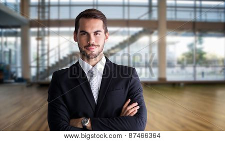 Smiling businessman posing with arms crossed against fitness studio