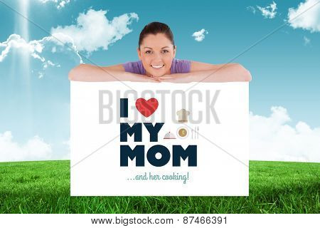 Good looking woman posing behind a billboard while standing against field and sky