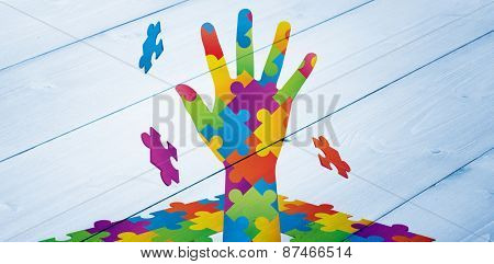 Autism awareness hand against bleached wooden planks background
