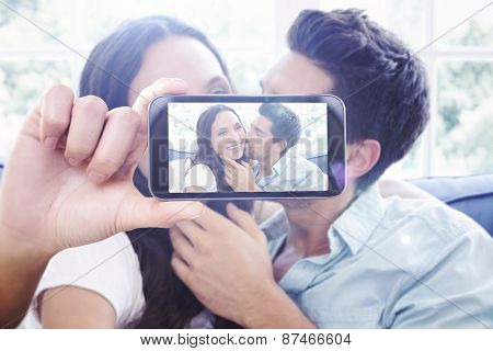 Hand holding smartphone showing against attractive couple cuddling on the couch