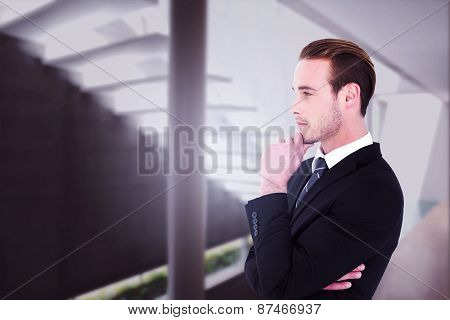 Thinking businessman standing with hand on chin against stylish modern home interior with staircase