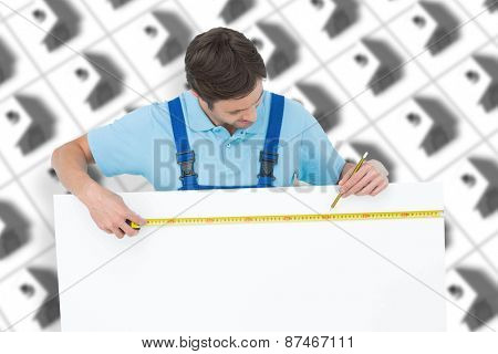Carpenter measuring blank bill board against one red roofed 3d house surrounded by many