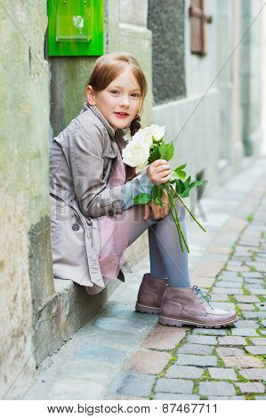 Outdoor portrait of a cute little girl with white roses