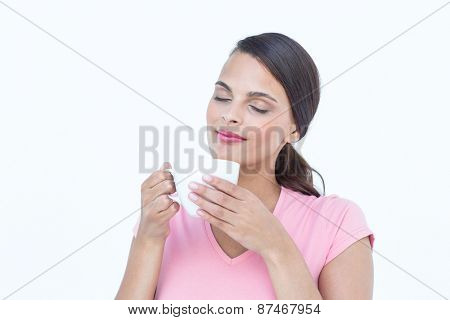 Beautiful woman smelling her coffee on white background