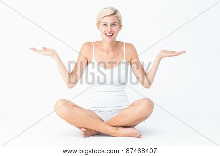 Happy blonde woman presenting something on white background