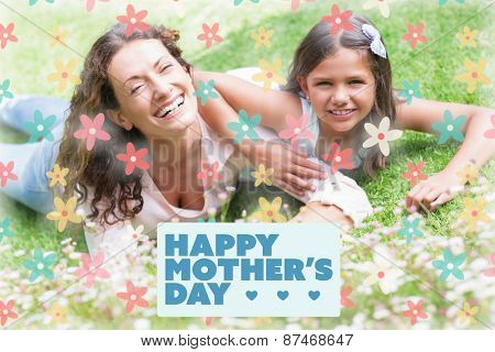 mothers day greeting against happy mother and daughter lying on the grass