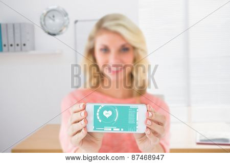 Pretty blonde showing her smartphone against a empty office with a laptop