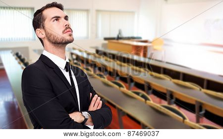 Thinking businessman with his arms crossed against empty seats with tables in a lecture hall