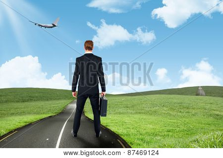 Rear view businessman standing with his briefcase against road leading out to the horizon