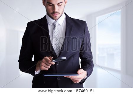Concentrated businessman using magnifying glass against bright white corridor with windows