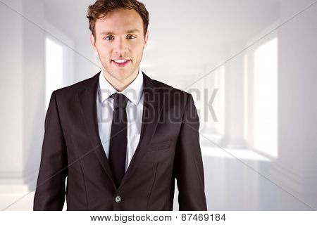 Young businessman smiling at camera against digitally generated room