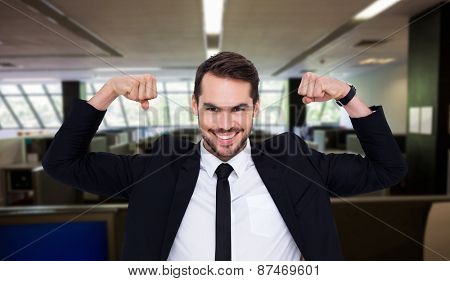 Happy businessman in suit cheering against empty office with separate units