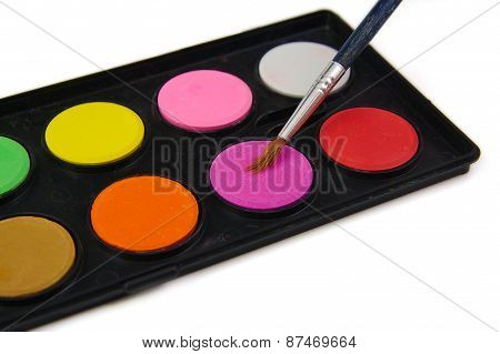 Watercolor paint and brush in black box on a white background