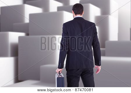 Rear view of businessman holding a briefcase against abstract white design
