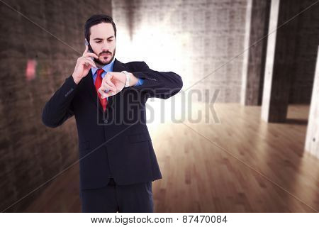 Serious businessman checking the time while on the phone against abstract room