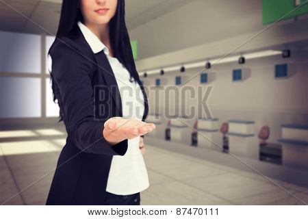 Pretty businesswoman presenting with hand against airport