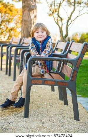 Funny little boy resting on a bench in the park, wearing blue waistcoat and shoes