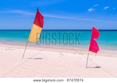 Red And Yellow-red Flags On The Empty Beach