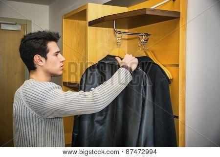 Handsome Man Hanging his Coats Inside his Wardrobe