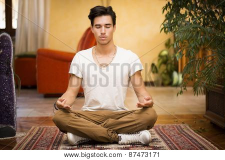 Young man meditating on his living room floor