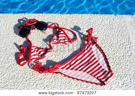 Women's Swimsuit, And Sunglasses Lying Near Swimming Pool.