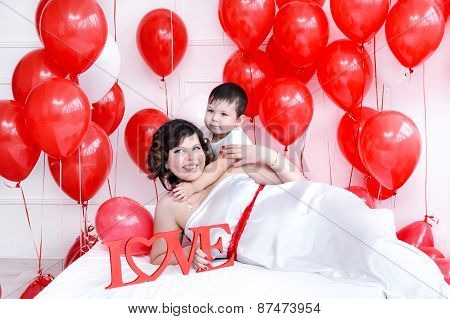 Young pregnant woman holding her son laying on a bed with love sign and red balloons around