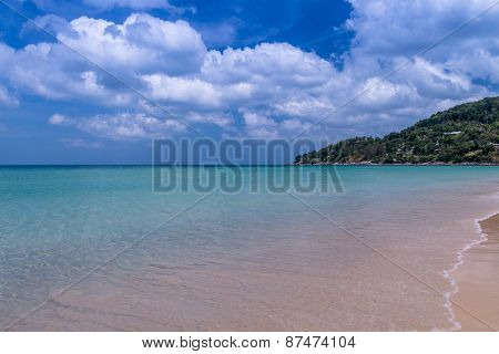 Sea Beach With Blue Sky And Yellow Sand And Some Clouds Above Landscape