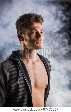 Handsome tough young man in dark hoodie on smoky background